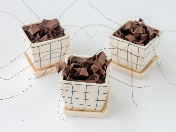 diys to do at home, three identical small plant pots, decorated with blue marker, and stuffed with brown paper strips, with strands of wire