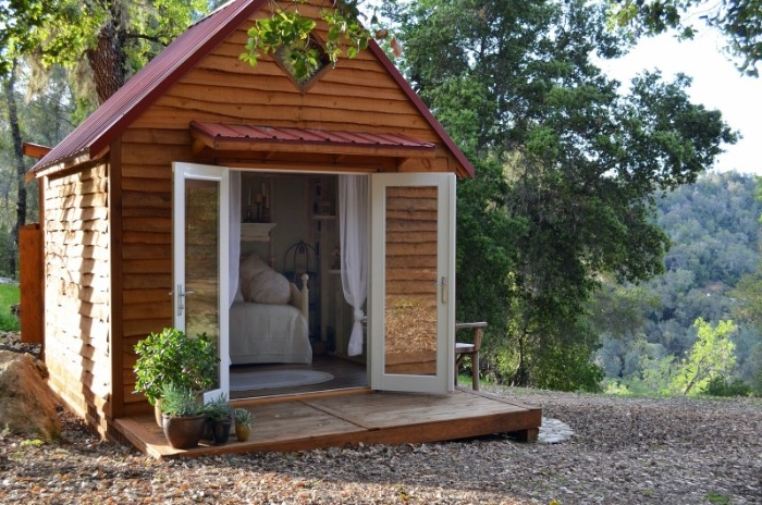 wooden shed ideas, small structure with open glass doors, built on a pebbled surface, and surrounded by trees