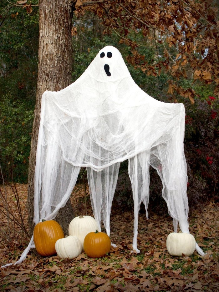 fall garden with fallen leaves, and several pumpkins, decorated with a ghost, made from sheer white fabric, with a simple, hand-painted face