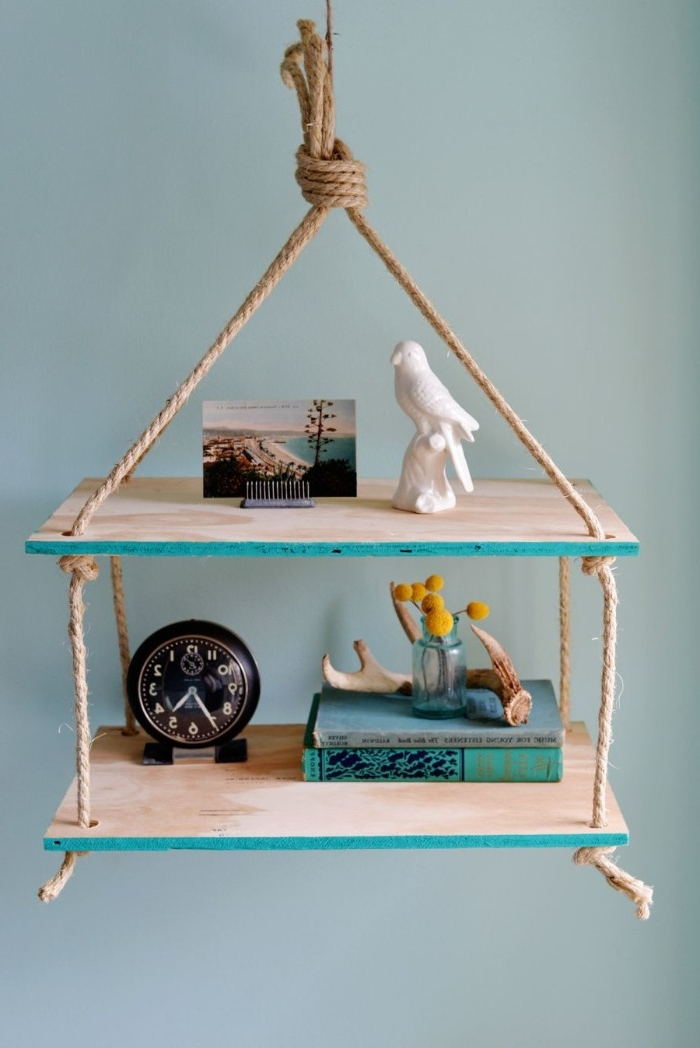 wooden shelves tied with rope, diys to do at home, hanging from the ceiling, of a room with blue walls