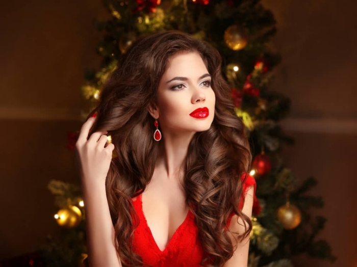 voluminous and long, wavy dark brunette hair, worn by a young woman, in a red dress, wearing red lipstick, red earrings and red nail polish