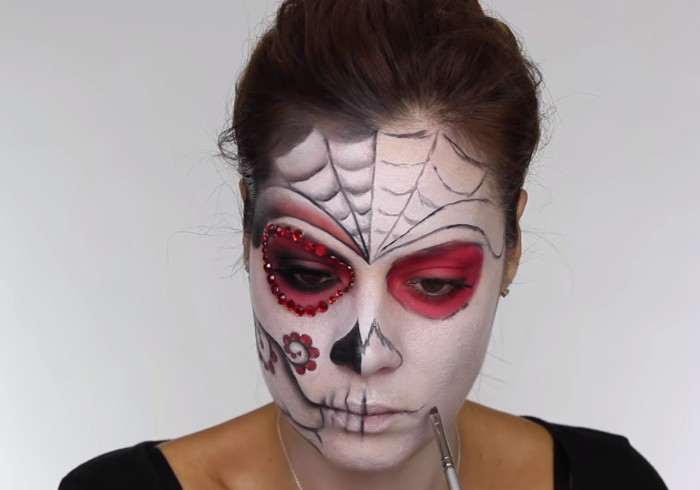 how to create a sugar skull, skeleton face paint, young woman drawing details with black, on her face, covered in white and pink paint