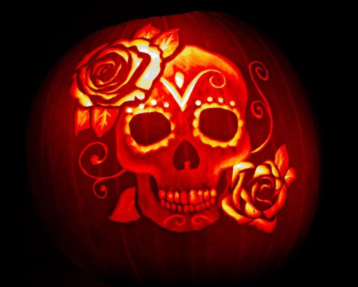 roses and a skull with ornaments, carved on an orange pumpkin, lit with candles from within, skeleton pumpkin, inspired by dia de los muertos