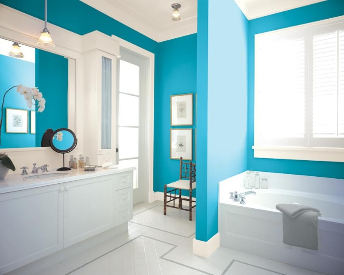 cerulean blue walls, with white plaster details, in a bright bathroom, with white furniture, best bathroom paint colors, white floor and a bathtub