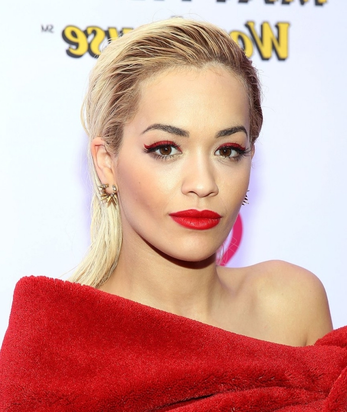 rita ora with slicked back wet-look blonde hair, wearing red eyeliner, and red lipstick, eye makeup for red lips, dressed in a plush red top