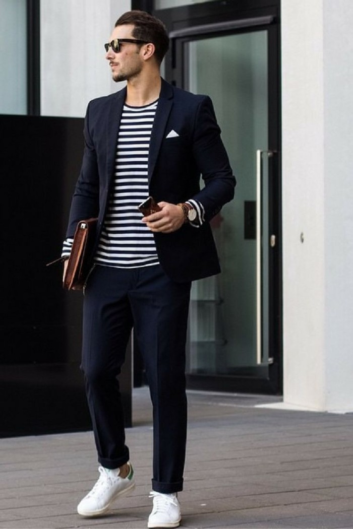 striped jumper in black and white, worn with a dark navy blazer, and matching smart, dark navy trousers, capsule wardrobe men, white sneakers and sunglasses