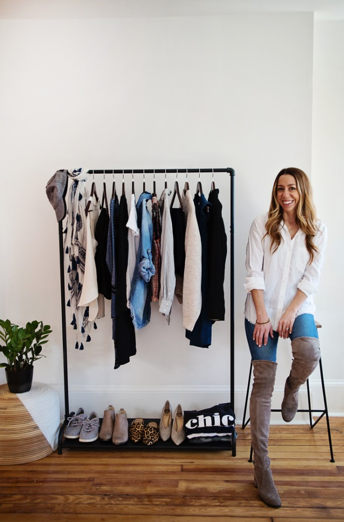 suede over the knee boots in pale grey, worn with blue skinny jeans, and a white blouse, capsule wardrobe essentials, on a smiling blonde woman, sitting next to a clothes rack