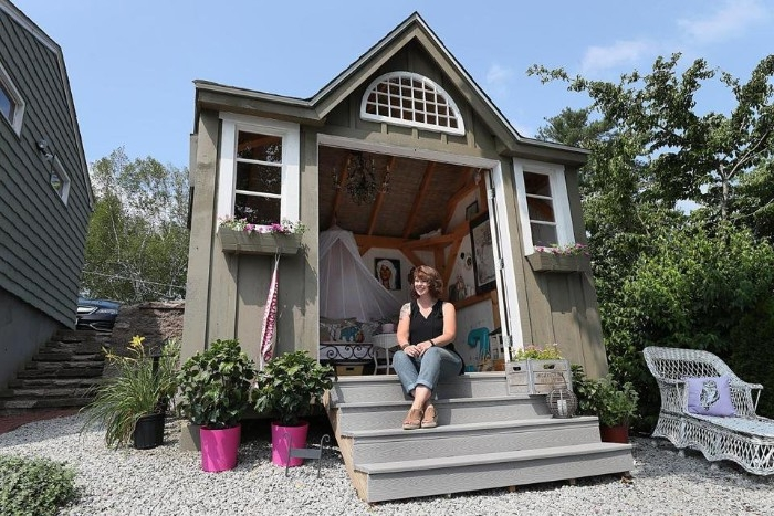 woman sitting on a small staircase, in front of a pale grey shed, with three windows, and open doors, shed ideas, furniture visible inside