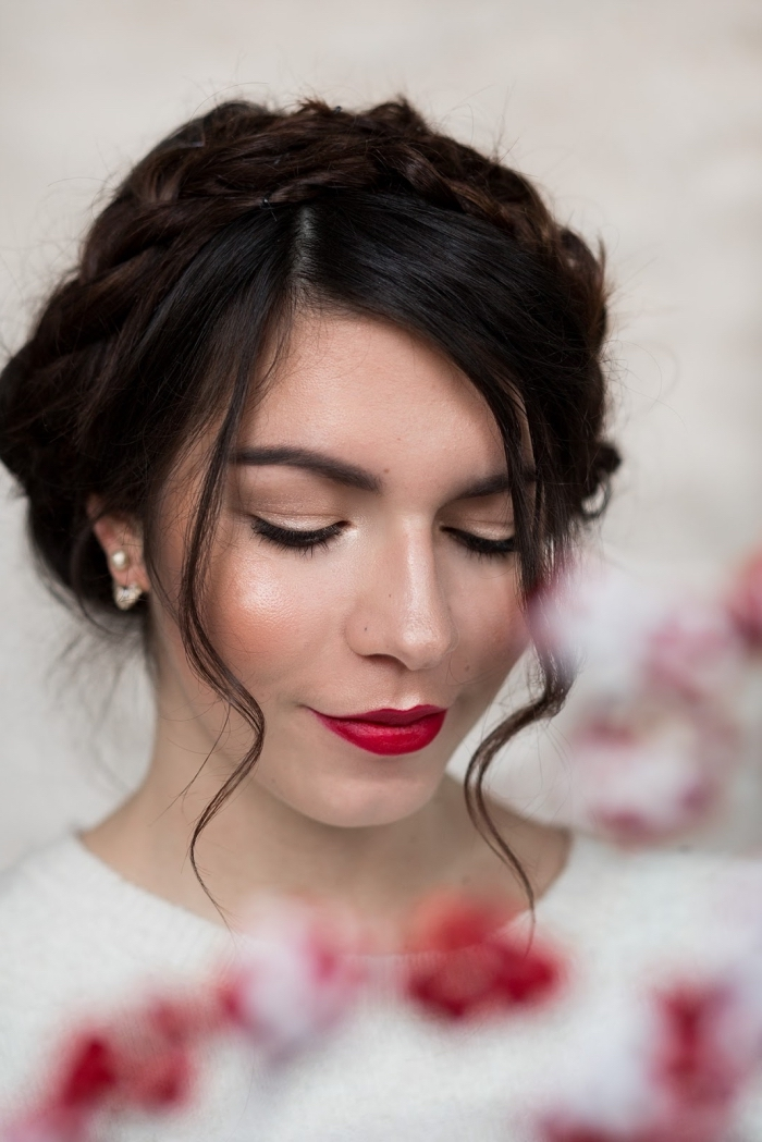 blush in peach pink, on the cheeks of a young woman, with dark brunette hair, wearing red lipstick, and a white top
