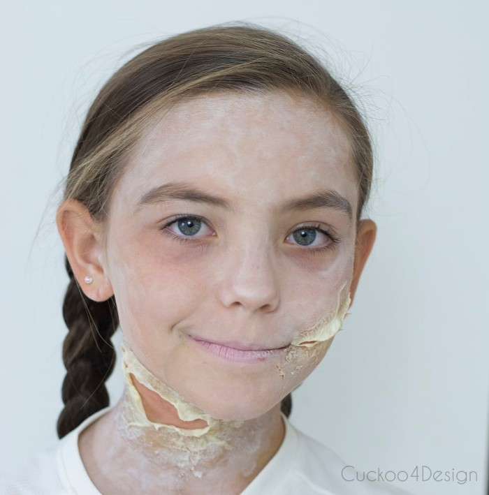 blue-eyed child, with brunette hair, braided in two pigtails, and face covered in powder-like white paint, scary face paint, with fake scars