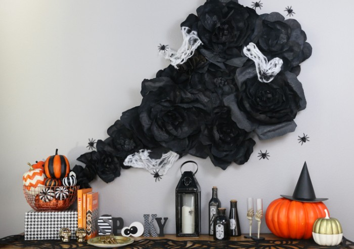 wall decoration made from black, white and grey fabric, made to look like smoke, haunted house decorations, surrounded by black plastic spiders, near a shelf with candles, painted pumpkins and other ornaments