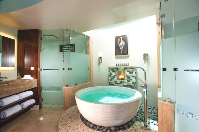 off-white round bathtub, filled with water, inside a room, with a shower cabin, bath remodel ideas, smooth grey stones under the tub
