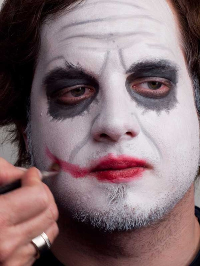 lipstick in red, smudged to create an exaggerated smile, on the face of a young man, wearing black and white joker face paint, halloween face paint ideas for adults