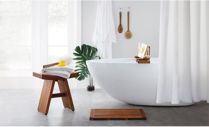 stool made of wood, with two towels, a body brush, and a rubber ducky, placed on a light grey floor, near a smooth white bathtub, bathroom picture ideas, green potted plant, and white curtains