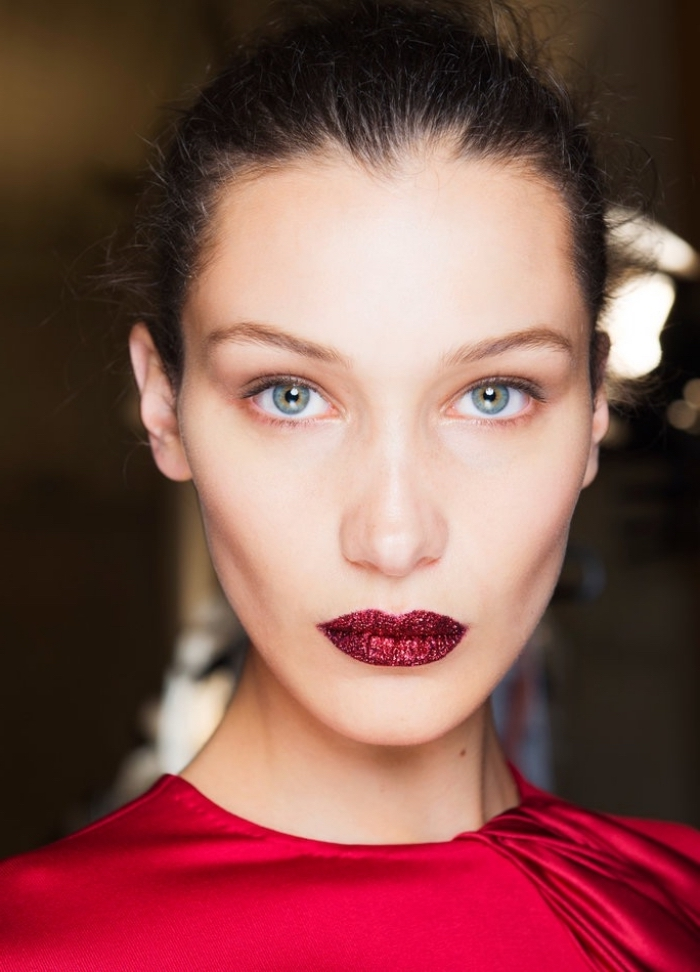 close up of a pale brunette woman, dressed in a red silky top, and wearing red lipstick, covered in glitter, christmas makeup