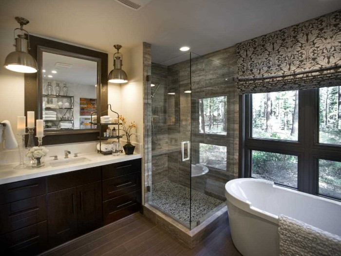 metallic lamps and a square wall mirror, above a dark brown cupboard, with a sink on top, glass shower cabin, and an oval tub nearby