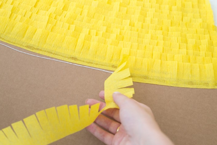 layers upon leyars, of frayed strips of yellow tissue paper, stuck on a piece of beige cardboard, couples halloween costumes, hand holding more yellow paper nearby