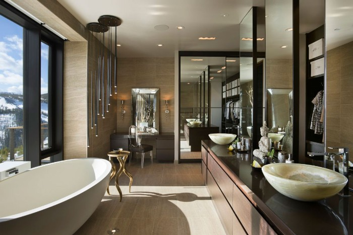 mirrored surfaces inside a large bathroom, with an oval white bathtub, dark brown cupboards, and ivory-colored sinks