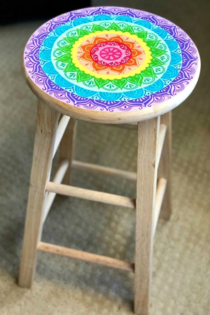 stool made from light wood, decorated with a mandala, painted in rainbow colors, diy room decor