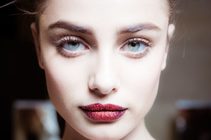 illuminated face of a young pale woman, with light blue eyes, wearing red lipstick, with red glitter