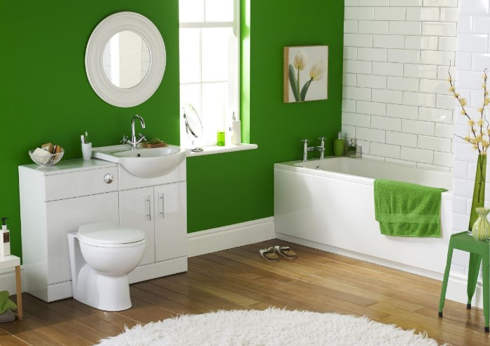 fluffy white rug, on a brown laminate floor, in a bathroom with one visible wall painted green, and the other covered in white subway tiles, white bathtub sink and toilet