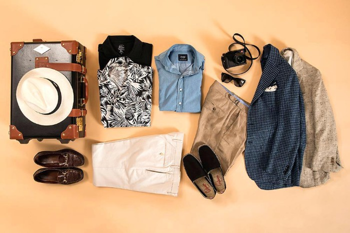 holiday capsule wardrobe men, two blazers and two pairs of trousers, in light colors, three button up shirts, loafers and espadrilles, a hat and sunglasses
