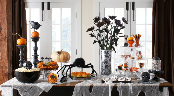flowers in black, in a vase, on a table, covered in fake cobwebs, with a big black spider ornament, black candlesticks, pumpkins and different snacks, haunted house decorations