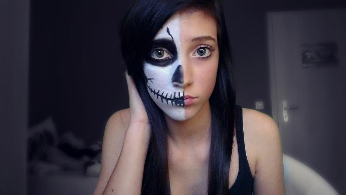 slim young girl, dressed in a black tank top, half of her face is painted to look like a skull, while the other half is left bare