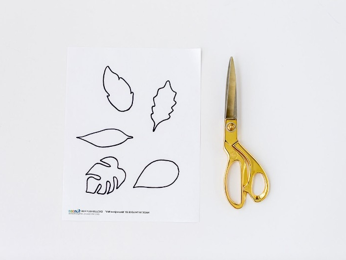 how to make diys for your room, a pair of scissors, with gold-colored handles, and a sheet of white paper, with several leaf outlines