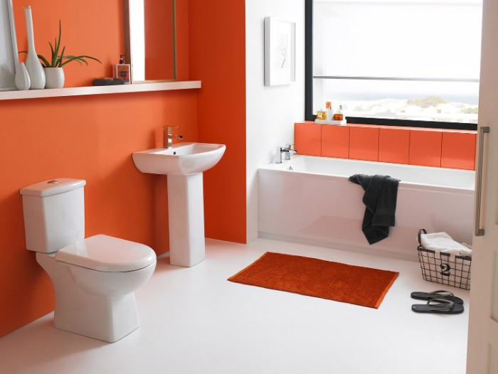 orange bathroom accent wall, in a bright room, containing a large window, a bathtub and a sink, a toilet and a small orange bath mat