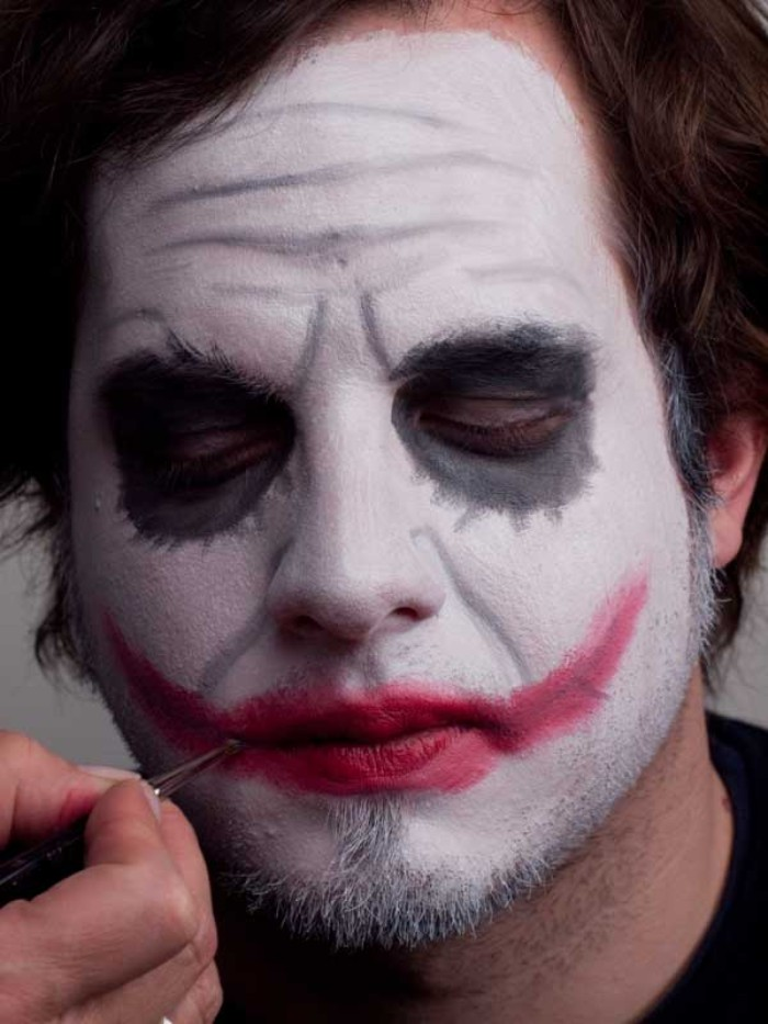 final touches added, on the face of a young man, painted in white, grey and red, to resemble the joker from batman, halloween face paint ideas for adults, halloween costumes inspired by movie villains