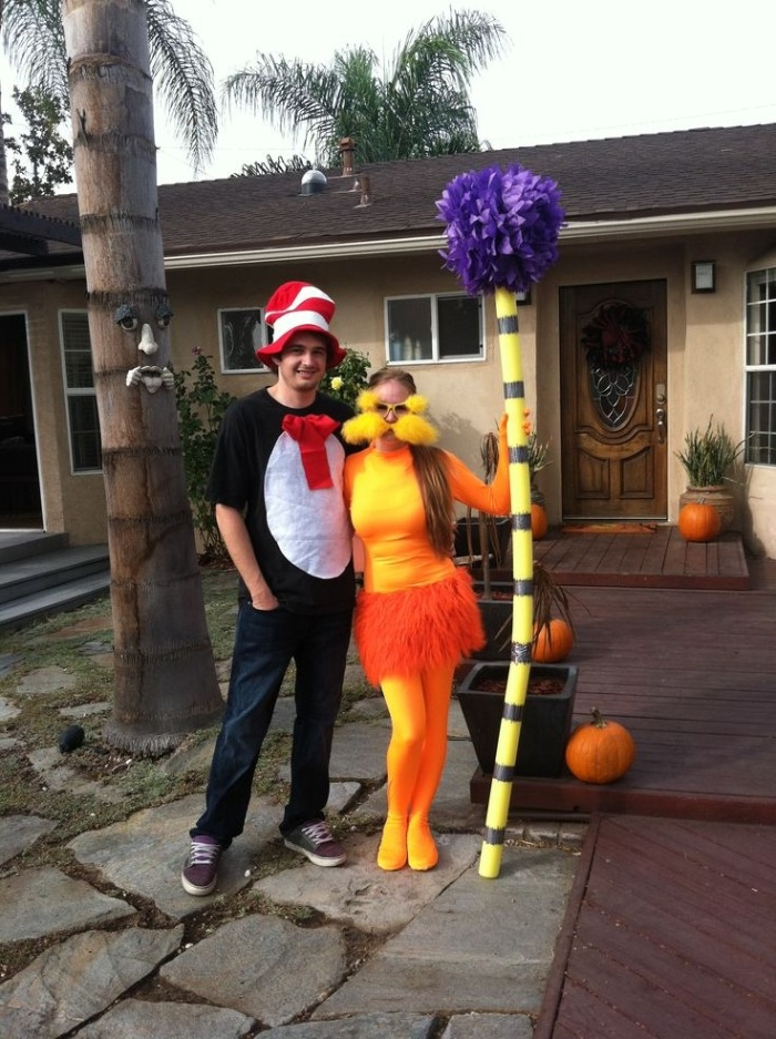 dr seuss character costumes, a man dressed like the cat in the hat, and a woman dressed like the lorax, standing in front of a house, funny couple halloween costumes
