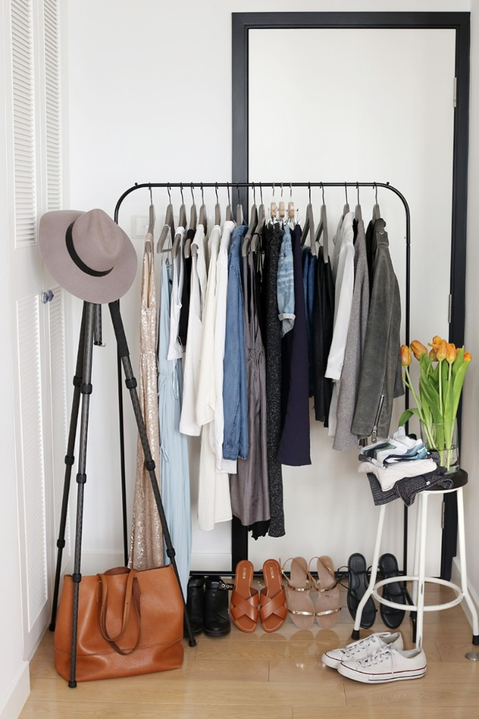 capsule wardrobe, black metal clothes rack, with several outfits on hangers, five pairs of shoes, a brown leather bag, and a grey hat