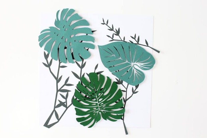 three different palm leaf shapes, cut out from paper in different shades of green, and stuck on top of a white piece of paper, with dark green branch-like shapes, diy bedroom décor