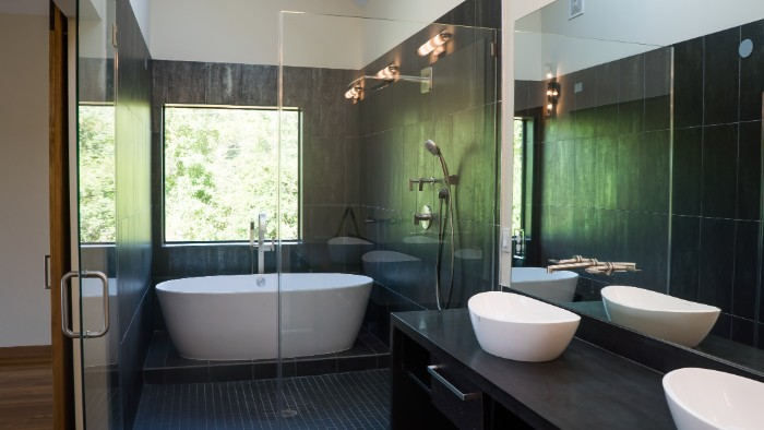 square window overlooking some greenery, inside a room with dark grey tiles, bath remodel ideas, white oval tub, and two white, boat-shaped sinks