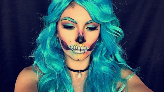 glam skull face paint, on a young woman, with long and wavy teal hair, and teal eyebrows, wearing matching teal eyeliner