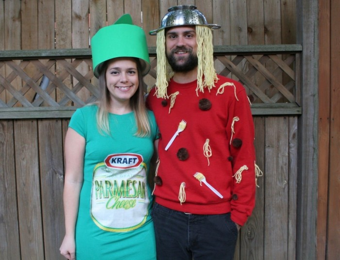 man with a colander, and some moodles on his head, dressed in a red jumper, decorated it faux spaghetti, forks and meatballs, funny couple halloween costumes, hugged by a smiling woman, dressed like parmesan
