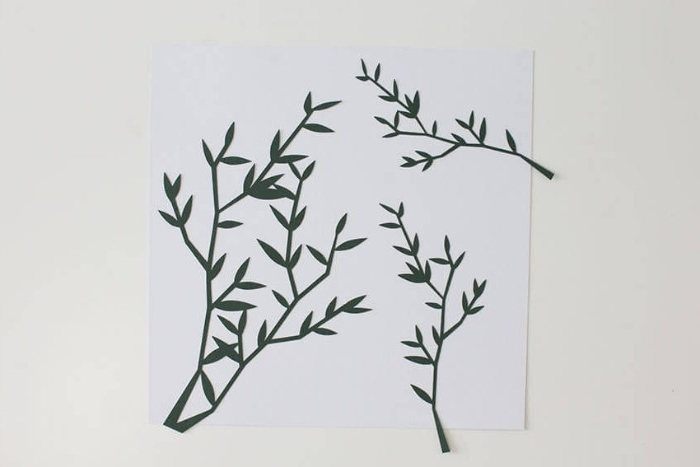 diy bedroom décor, for your walls, three dark green, branch-shaped paper cutouts, stuck on a white, square piece of paper,