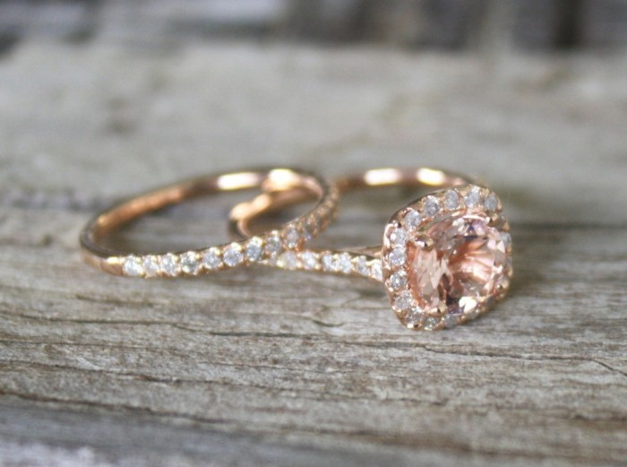 close up of two gold rings, one features a large pink diamond, and several small white diamonds, and the other is encrusted in small white diamonds