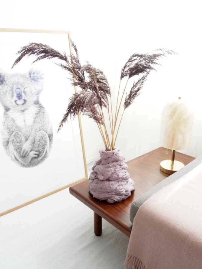koala artwork in a frame, near a wooden table, with a vase, made from pale pink expanding foam, diys to do at home, containing dried decorative plants