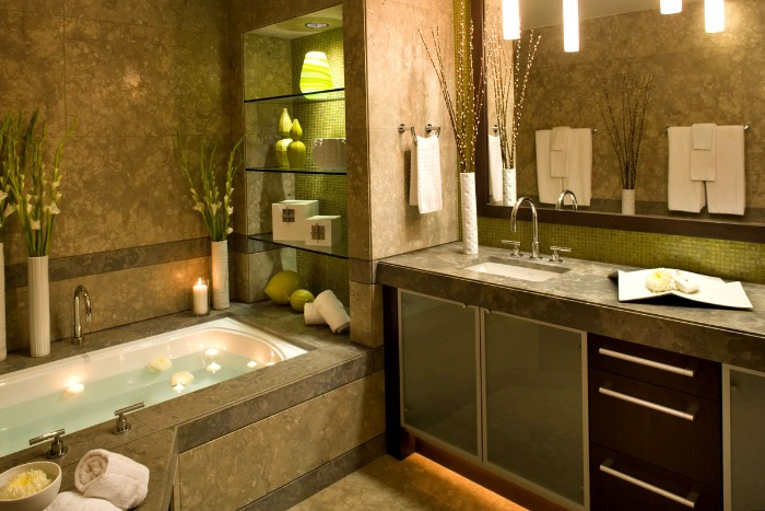 green and brown tiles, decorating the walls, of a bathroom, with an elevated bath, filled with water, and containing several floating lit candles