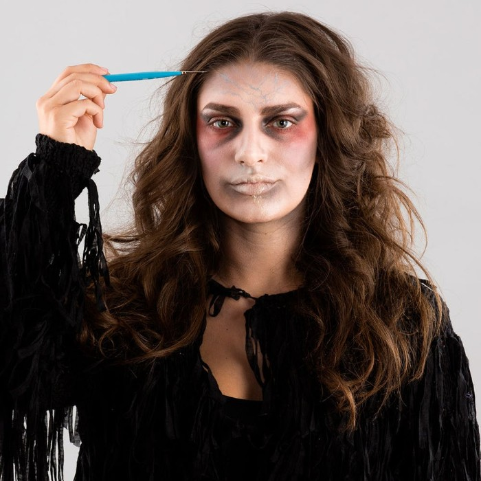 small and thin brush, used to paint little blue and red veins, on the forehead of a woman, wearing zombie face paint, halloween ideas for grownups