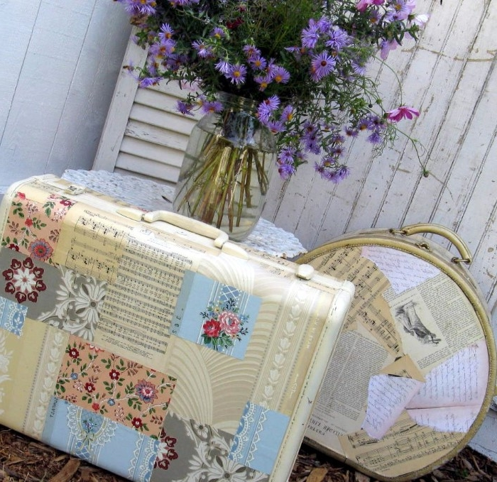 glass jar containing blue wild flowers, placed on a table, near two vintage suitcases, decorated with decoupage