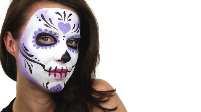 heart shape and floral motifs, decorating a sugar skull face paint, in white and black, pink and violet, on the face of a brunette woman
