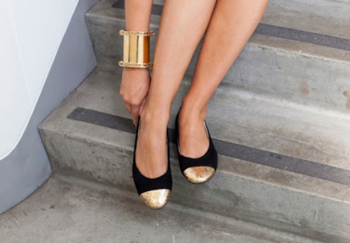 ballet flats in black, with gold glitter toe details, worn by a pair of slim legs, what is a capsule wardrobe, arm with a golden cuff bracelet