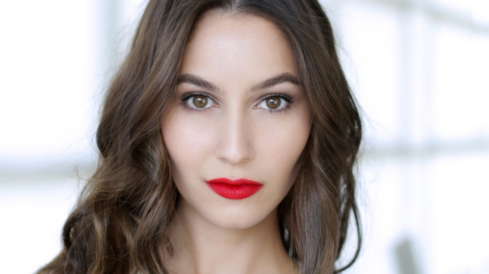 chocolate brunette wavy hair, on a pale, brown-eyed woman, wearing bright red lipstick, and black mascara