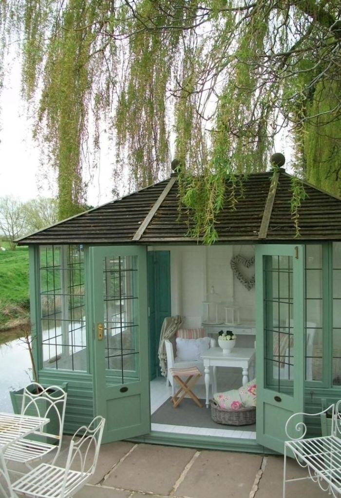 mint green garden shed, with large windows, and open double doors, containing a small white coffee table, a chair and other furniture, weeping willow growing next to it