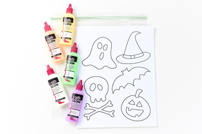 materials needed for creating diy, glow-in-the-dark stickers, halloween decorations, five small tubes of glow-in-the-dark paint, a clear zip bag, and a piece of white paper, with halloween-themed shapes