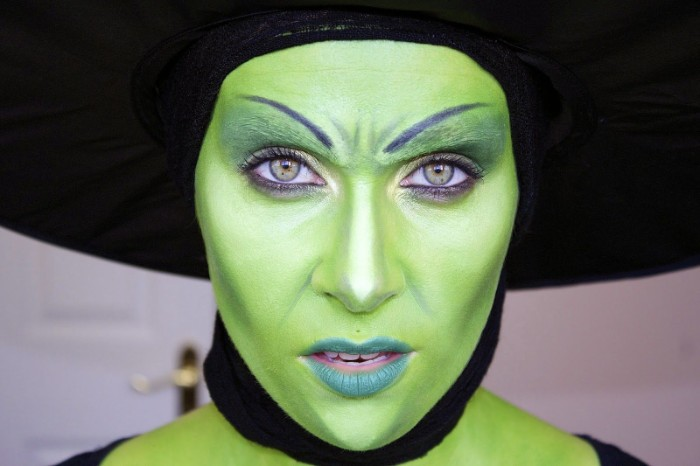 witch face paint, woman with face covered in green paint, wearing bluish green lipstuck, and a large black hat