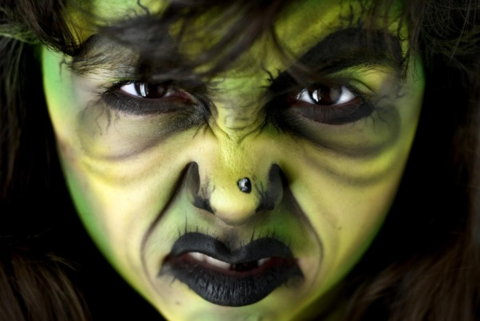 angry looking woman, with witch face paint, in green and yellow and black, wrinkles and large eyebrows, a fake black mole